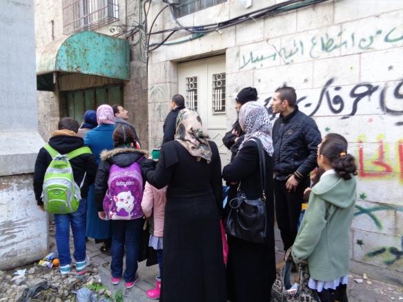 professoras e criancas sendo revistadas para irem a escola